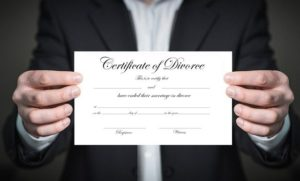 Man's hands holding divorce certificate