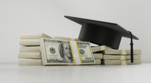 Graduation cap with cash; pay off student loans while saving for retirement